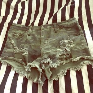 Distressed camo denim booty shorts on trend